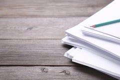 Het schrijven concept - verfrommelde omhoog document pakjes met een blad van Witboek en potlood op grijze houten achtergrond royalty-vrije stock afbeeldingen
