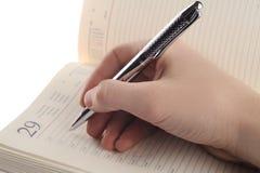 het schrijven in een notitieboekje Royalty-vrije Stock Afbeeldingen