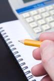 Het schrijven in een verbindend notitieboekje. Stock Foto