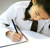 Het schrijven in haar thuiswerkboek. Royalty-vrije Stock Foto