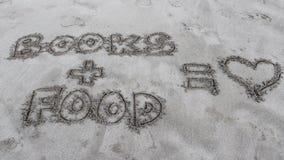 Het schrijven in het zand over boeken en voedsel Royalty-vrije Stock Foto's
