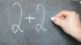 Het schrijven in krijt op een bord De les van Math stock videobeelden