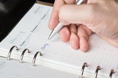 Het schrijven met zilveren pen op open bedrijfsagenda Stock Foto
