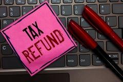Het schrijven nota die Belastingsterugbetaling tonen Bedrijfsfoto toegepaste demonstratie wanneer de geldaansprakelijkheid minder royalty-vrije stock foto's