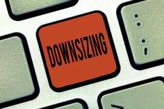 Het schrijven nota die 'downsizing' tonen De bedrijfsfoto demonstratie maakt een bedrijf kleiner door de vermindering van persone stock foto's