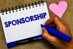 Het schrijven nota die Sponsoring tonen Bedrijfsfoto demonstrerend Persoon of bedrijf die de financiële materiële Blocnote van de royalty-vrije stock fotografie