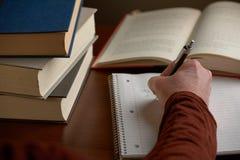 Het schrijven nota's met boeken op bureau stock afbeeldingen