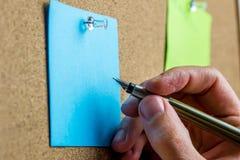 Het schrijven op blauw post-itdocument Royalty-vrije Stock Foto