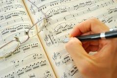 Het schrijven op een muziekscore Stock Foto's