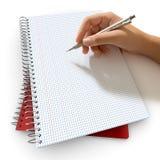 Het schrijven op een notitieboekje Stock Foto