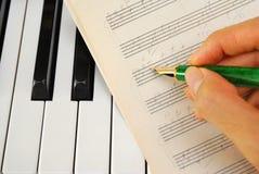 Het schrijven op oude muziekscore met pen op toetsenbord Royalty-vrije Stock Afbeelding