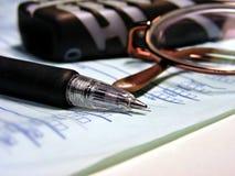 Het schrijven: pen, glazen en cellphone Stock Afbeelding