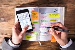 Het Schrijven van Businesspersonwith mobile phone Programma in Agenda royalty-vrije stock fotografie