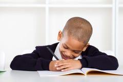Het schrijven van de schooljongen thuiswerk Stock Afbeeldingen
