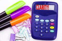 Het schrijven van de tekst van de woordduidelijkheid in het bureau met omgeving zoals teller, pen die op calculator schrijven Bed royalty-vrije stock afbeelding