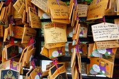 Het schrijven van een wens op een kleine houten plaqueEma en het hangen van het onder de wensen van andere bezoekers royalty-vrije stock afbeeldingen