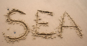 Het schrijven van het zand - OVERZEES Royalty-vrije Stock Afbeeldingen