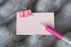 Het schrijven van roze pen op lichtrose sticker met de roze kantoorbehoeften van de metaalklem royalty-vrije stock fotografie
