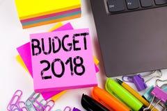 Het schrijven van tekst die Begroting 2018 tonen maakte in het bureau met omgeving zoals laptop, teller, pen Bedrijfsconcept voor Stock Foto's