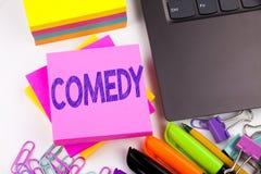 Het schrijven van tekst die Komedie tonen maakte in het bureau met omgeving zoals laptop, teller, pen Bedrijfsconcept voor Tribun stock afbeeldingen