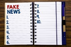 Het schrijven van tekst die Vals Nieuws tonen Bedrijfsdieconcept voor Hoax Journalistiek op het document van de notitieboekjenota stock fotografie