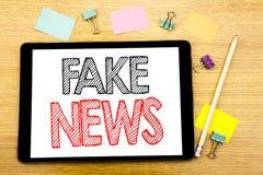 Het schrijven van tekst die Vals Nieuws tonen Bedrijfsdieconcept voor Hoax Journalistiek op tabletlaptop wordt geschreven, houten stock foto