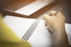 Het schrijven van zuivelfabriek op notitieboekje stock foto's