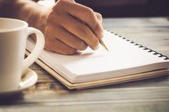 Het schrijven van zuivelfabriek op notitieboekje in koffiewinkel, concept als geheugen van het leven stock afbeeldingen