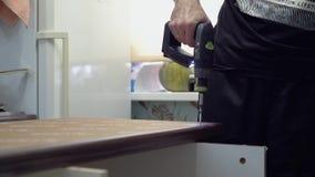 Het schroeven van de schroef in de lijstoppervlakte met een schroevedraaier E Close-up stock videobeelden