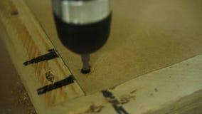 Het schroeven van een schroef in een ladeagent aan kant van houten lade die een batterijboor gebruiken Meubilairassemblage Hoofdb stock videobeelden