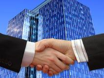 Het schudden van zakenlieden dient voorzijde in de Wolkenkrabber Stock Afbeelding