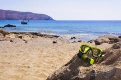 Het scuba-uitrustingsmasker en snorkelt op de rots met blauwe overzees op achtergrond stock foto's