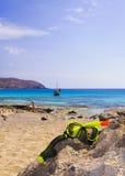 Het scuba-uitrustingsmasker en snorkelt op de rots met blauwe overzees op achtergrond Stock Afbeeldingen