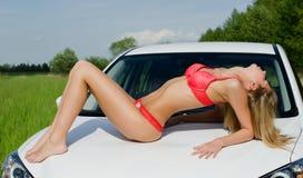 Het seksuele meisje in roze bikini met witte auto royalty-vrije stock fotografie
