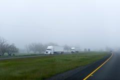 Het semi konvooi van de de installatieslading van vrachtwagensaanhangwagens grote op mistige weg Royalty-vrije Stock Foto's