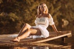 Het sensuele aantrekkelijke vrouw stellen door het meer bij zonsondergang of zonsopgang stock foto's