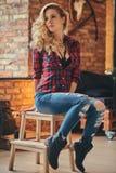 Het sensuele blonde hipster meisje met lang krullend haar gekleed in een vachtoverhemd en jeans houdt een kop van ochtendkoffie stock foto