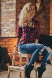 Het sensuele blonde hipster meisje met lang krullend haar gekleed in een vachtoverhemd en jeans houdt een kop van ochtendkoffie royalty-vrije stock foto's