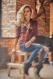 Het sensuele blonde hipster meisje met lang krullend haar gekleed in een vachtoverhemd en jeans houdt een kop van ochtendkoffie royalty-vrije stock afbeeldingen