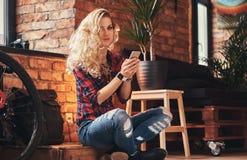 Het sensuele blonde hipster meisje met lang krullend haar gekleed in een vachtoverhemd en jeans houdt een smartphonezitting op a Stock Afbeeldingen