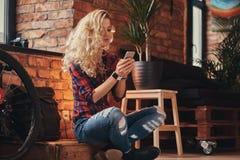 Het sensuele blonde hipster meisje met lang krullend haar gekleed in een vachtoverhemd en jeans houdt een smartphonezitting op a Royalty-vrije Stock Foto's