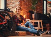 Het sensuele blonde hipster meisje met lang krullend haar kleedde zich in een vachtoverhemd en jeans zittend op een houten doos,  Stock Afbeelding