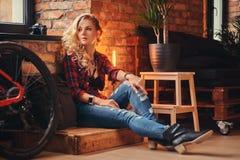 Het sensuele blonde hipster meisje met lang krullend haar kleedde zich in een vachtoverhemd en jeans zittend op een houten doos,  Royalty-vrije Stock Foto's
