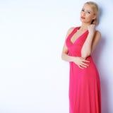 Het sensuele blonde vrouw stellen in roze kleding Stock Afbeeldingen