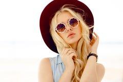 Het sensuele blondemeisje met ronde bloemenzonnebril, krullend haar, grote lippen en hoed raakt eigen haar en het bekijken camera stock foto's