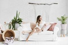 Het sensuele en mooie blonde modelmeisje in modieuze glazen en modieuze satijnpyjama's, zit op de witte bank met hoofdkussens en royalty-vrije stock afbeeldingen