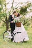 Het sensuele jonge jonggehuwdepaar kussen in park met de fiets van de bruidegomholding royalty-vrije stock foto's