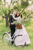 Het sensuele jonge jonggehuwdepaar stellen in zonnig park met fiets royalty-vrije stock fotografie