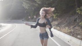 Het sensuele meisje hipster met het roze haar dragen breit bustehouder en overhemd lopend op de weg op een bergachtig gebied met  stock footage