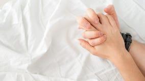 Het sensuele mooie jonge paar heeft geslacht op bed Vrouwelijke hand die witte bladen in vervoering, orgasme trekken Het concept  stock foto's